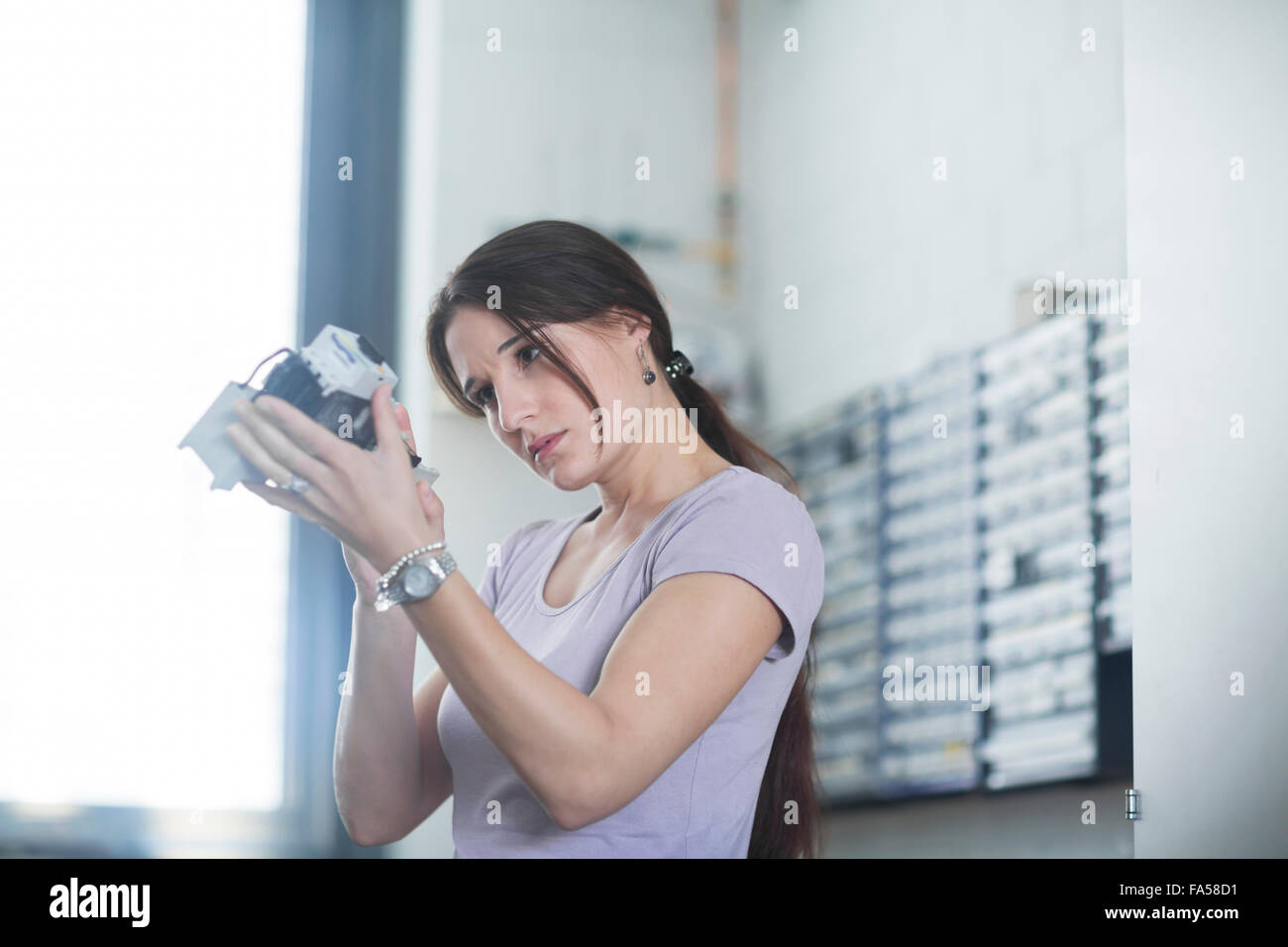 Female technician examining electrical component in an industrial plant, Freiburg Im Breisgau, Baden-Württemberg, - Stock Image