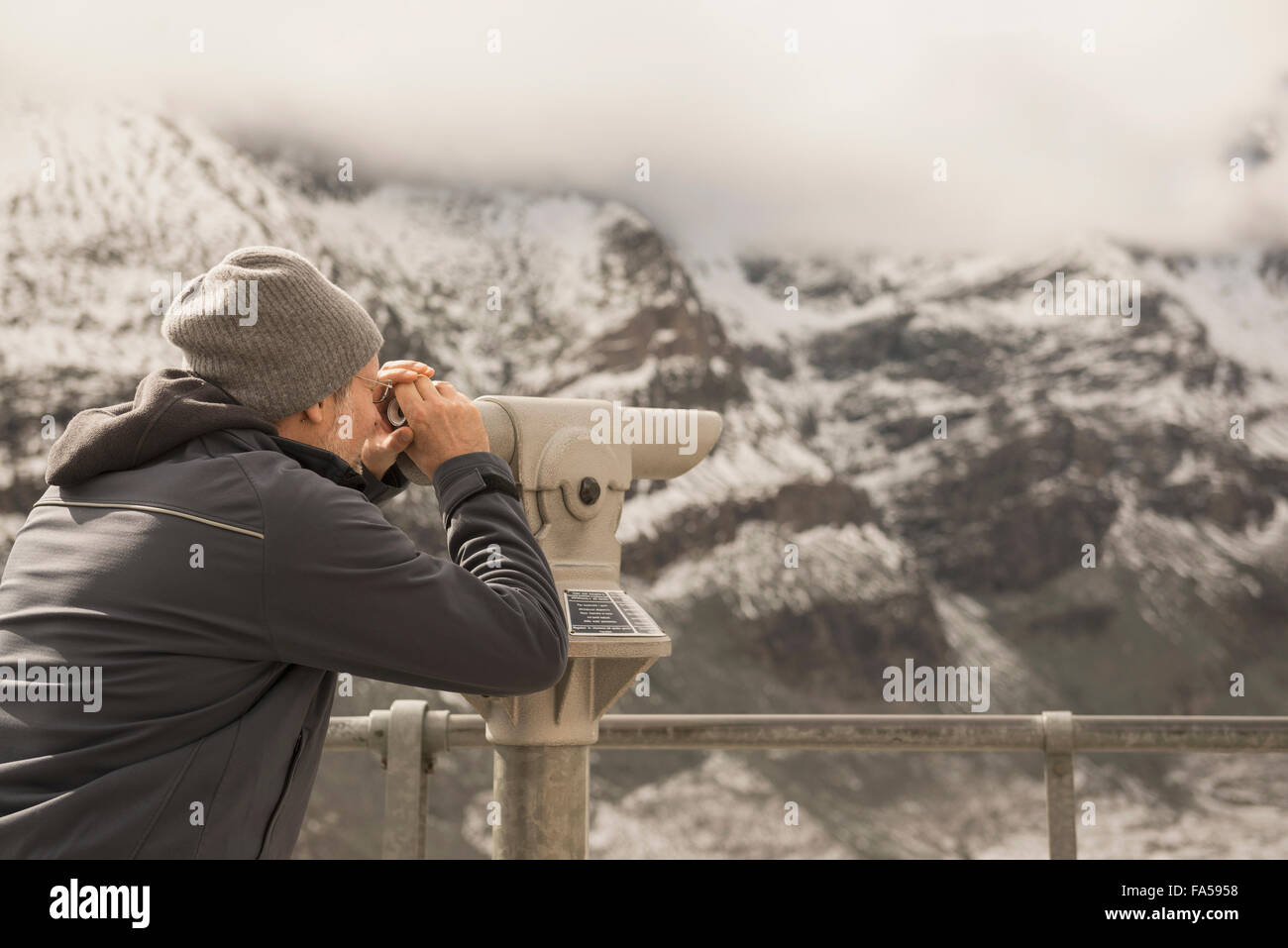 Mature man looking at mountain with telescope, Grossglockner mountain, National Park Hohe Tauern, Carinthia, Austria - Stock Image