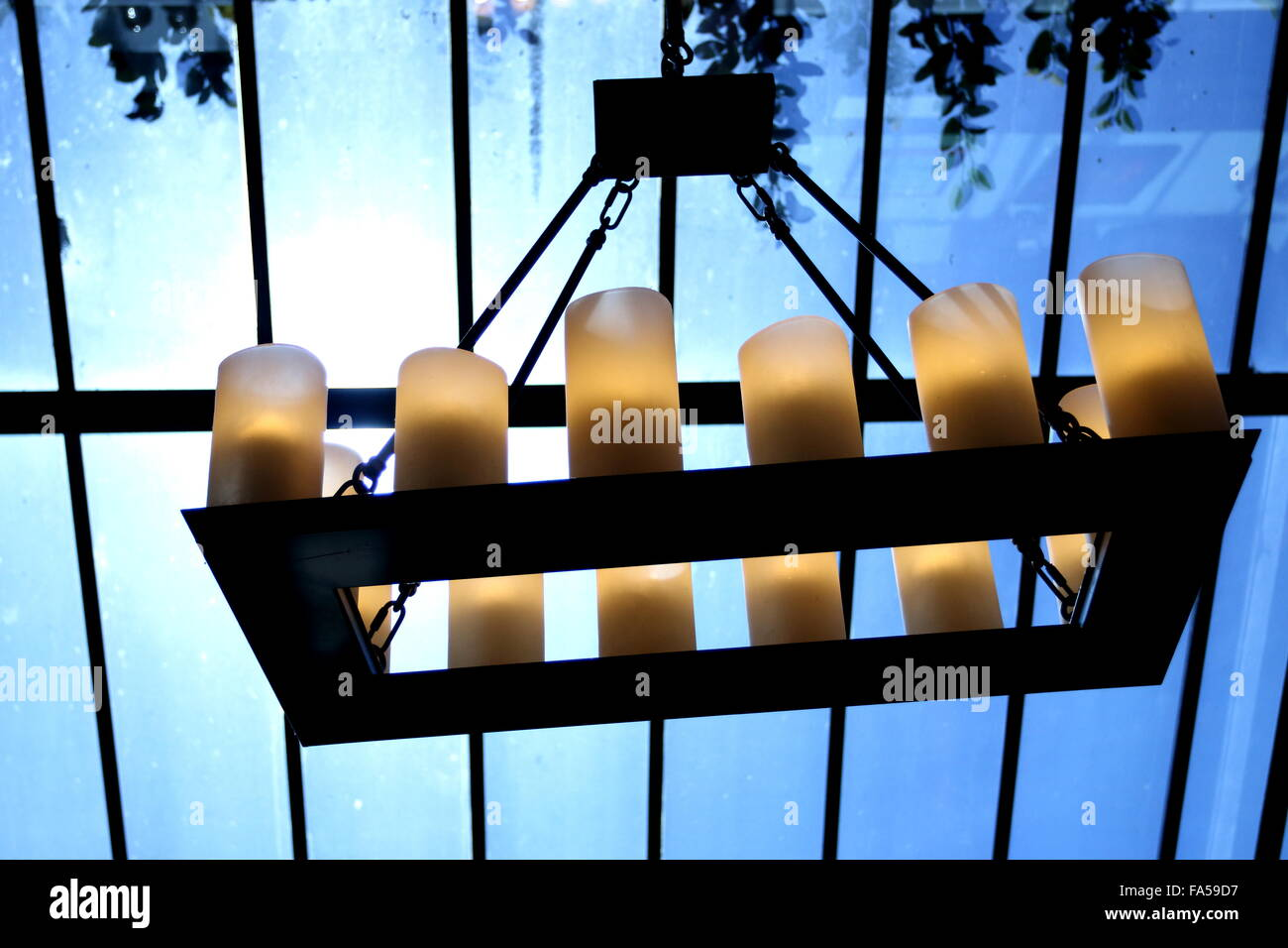 Hanging unlit candles near the clear glass ceiling - Stock Image