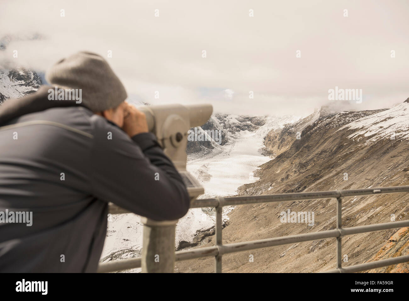 Mature man looking at view with telescope, Pasterze glacier, National Park Hohe Tauern, Carinthia, Austria Stock Photo
