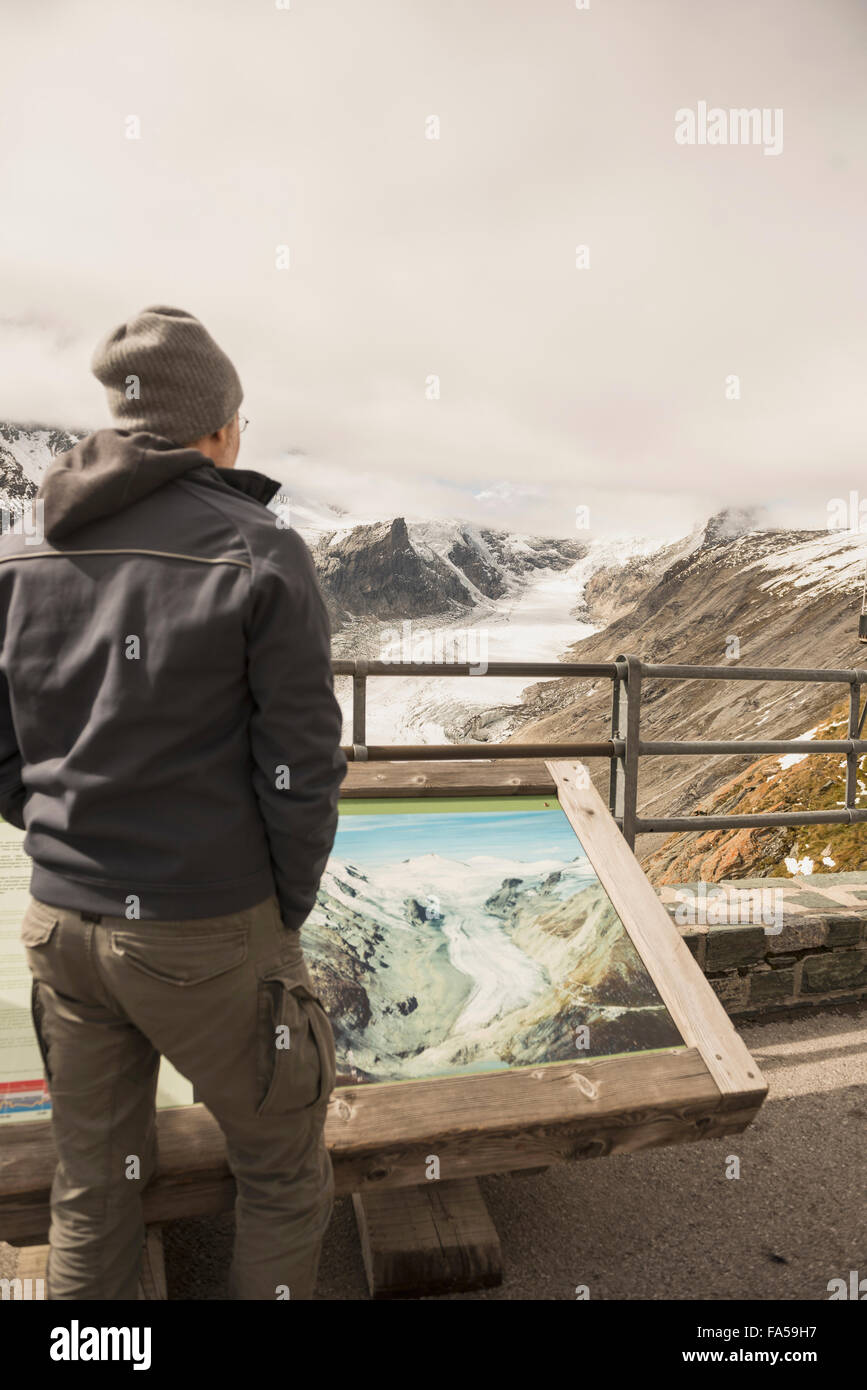 Mature man comparing the melting Grossglockner glacier and stream with a former image in a display cabinet, Carinthia, - Stock Image