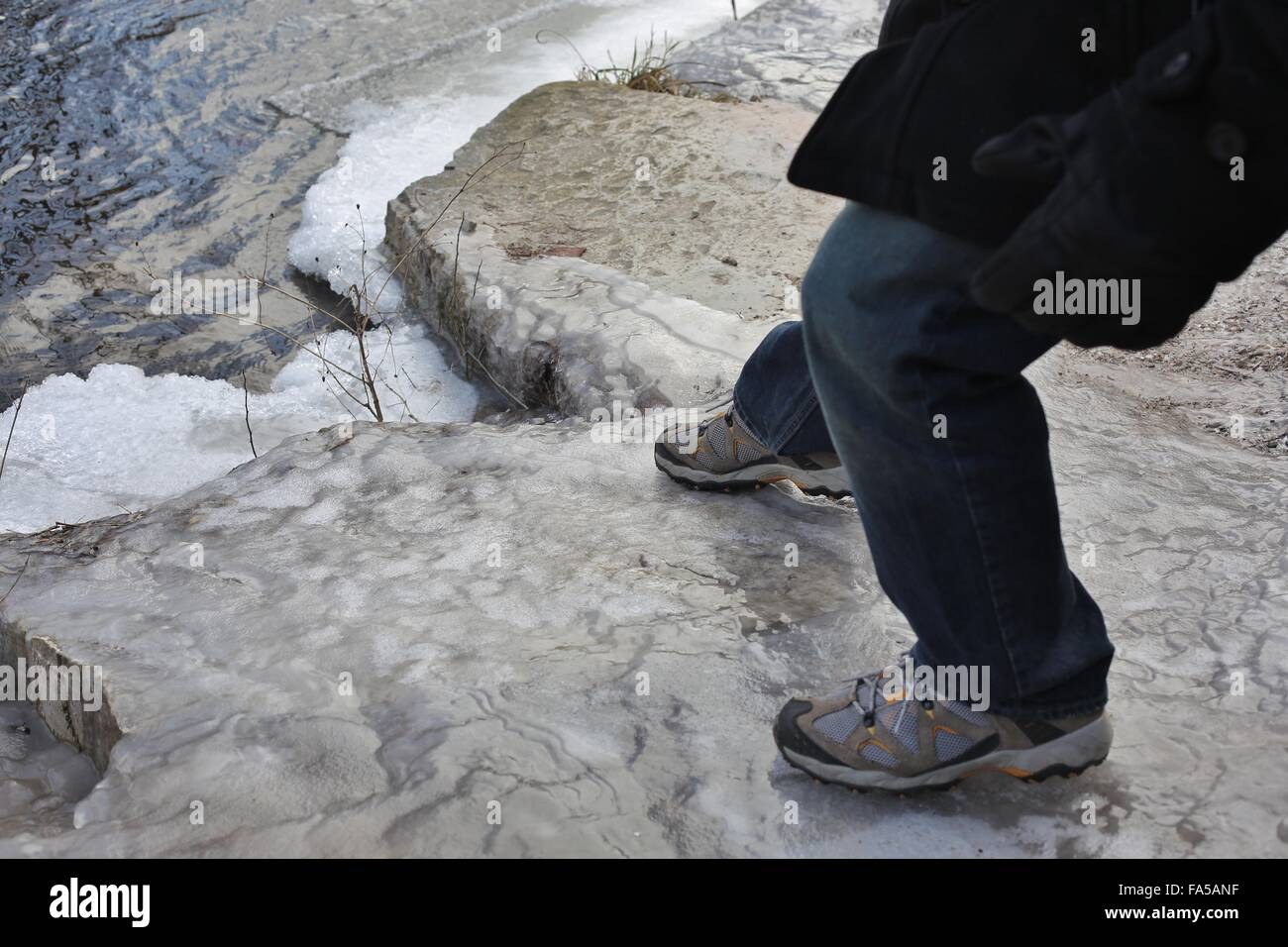 A man slipping on an icy rock. - Stock Image