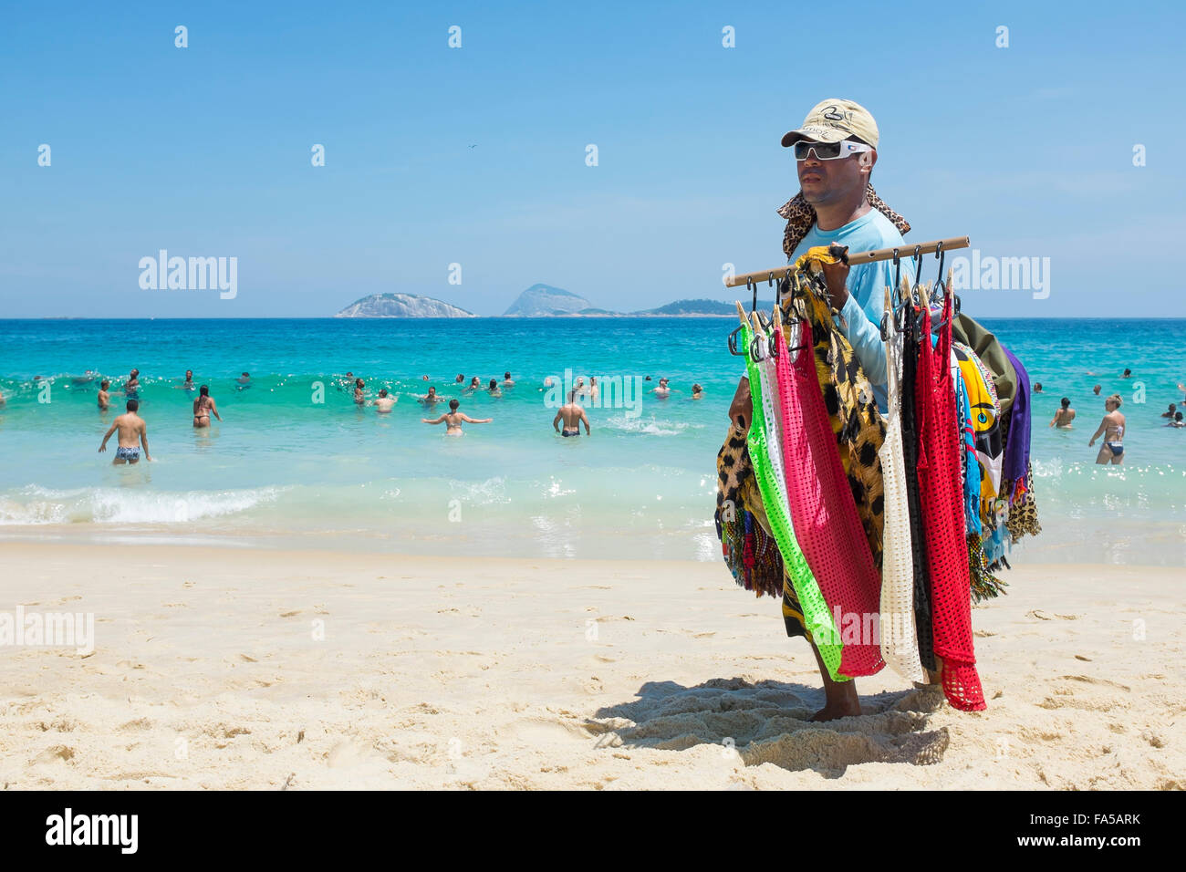 RIO DE JANEIRO, BRAZIL - MARCH 15, 2015: A beach vendor selling brightly colored kanga sarongs carries merchandise - Stock Image