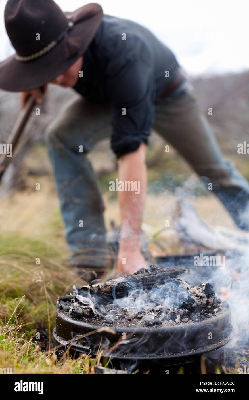 Clay Baird of Bogong Horseback Adventures prepares dinner on the campfire in the Bogong High Plains. - Stock Image