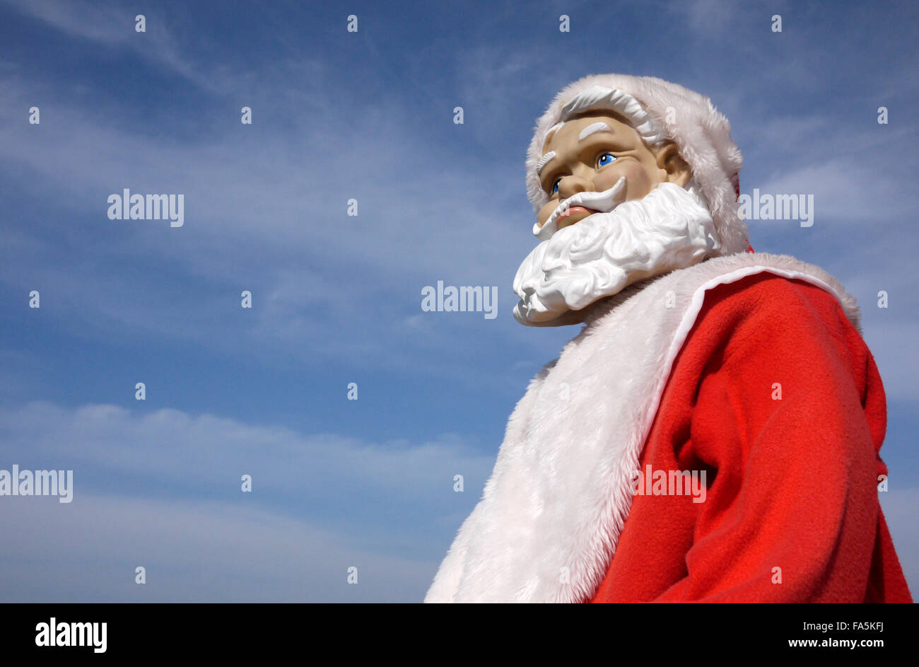 A Santa Claus manikin with a frowning worried apprehensive looking expression pictured outdoors under a blue sky - Stock Image