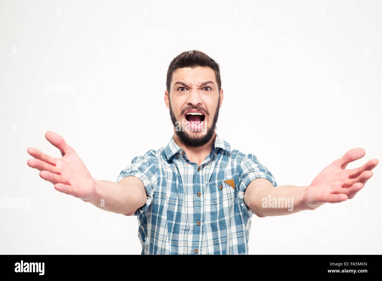 Funny concentrated young man with beard in checkered shirt singing loudly over white background - Stock Image