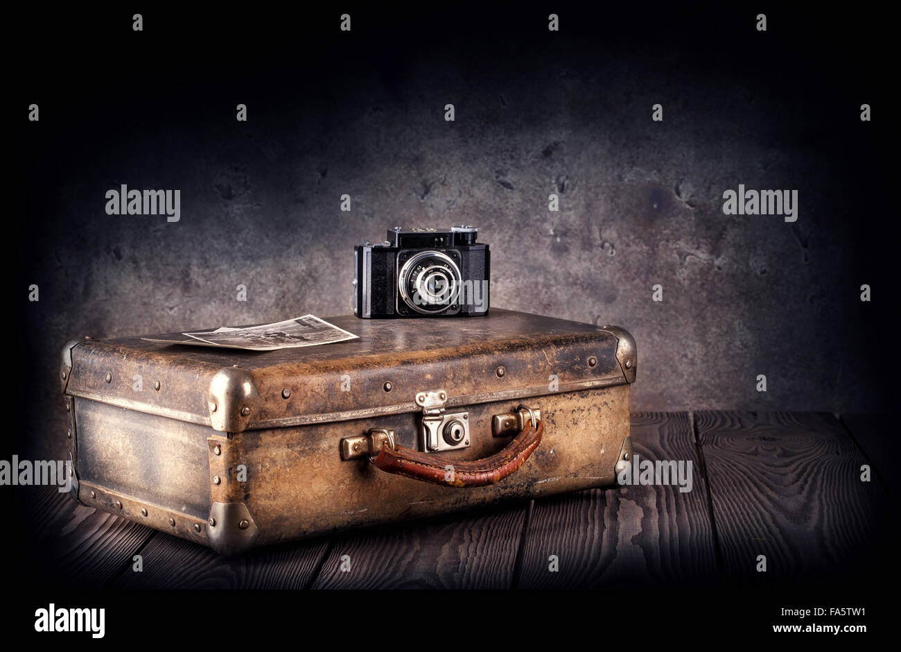 Old suitcase with a camera and photos on wooden background - Stock Image