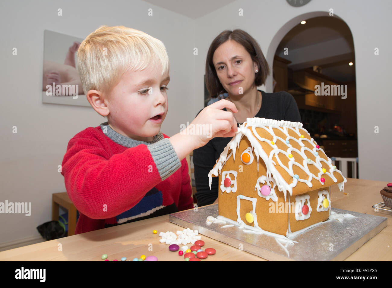 5 year old boy building a Gingerbread house made of gingerbread ahead of the Christmas festivities, UK - Stock Image