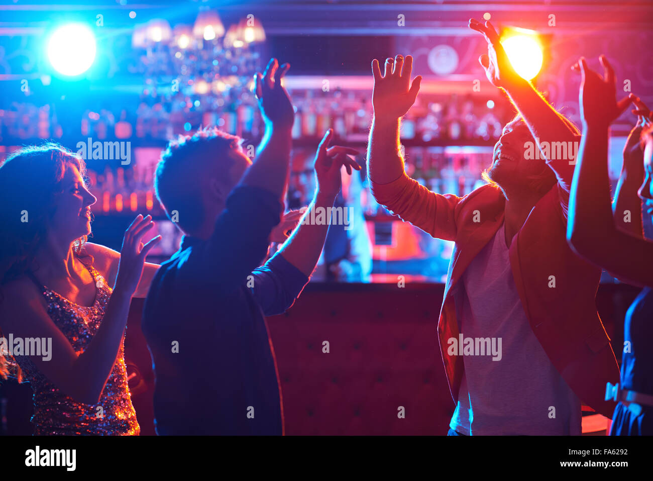 Happy dancers enjoying disco in night club - Stock Image