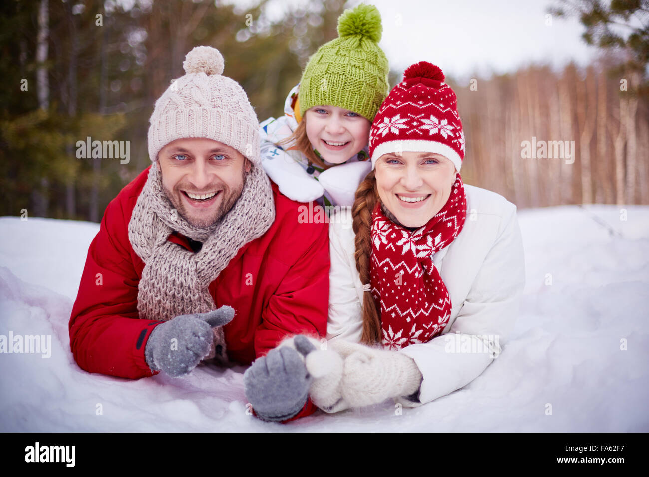 Happy family lying in snowdrift in winter forest - Stock Image