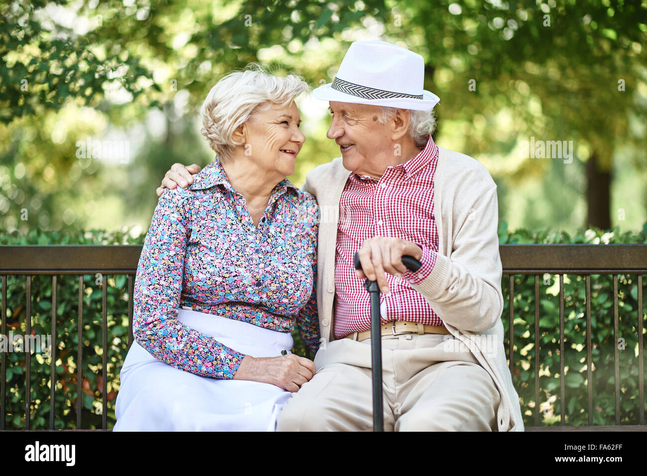 Happy seniors sitting on bench in the park and enjoying summer day - Stock Image