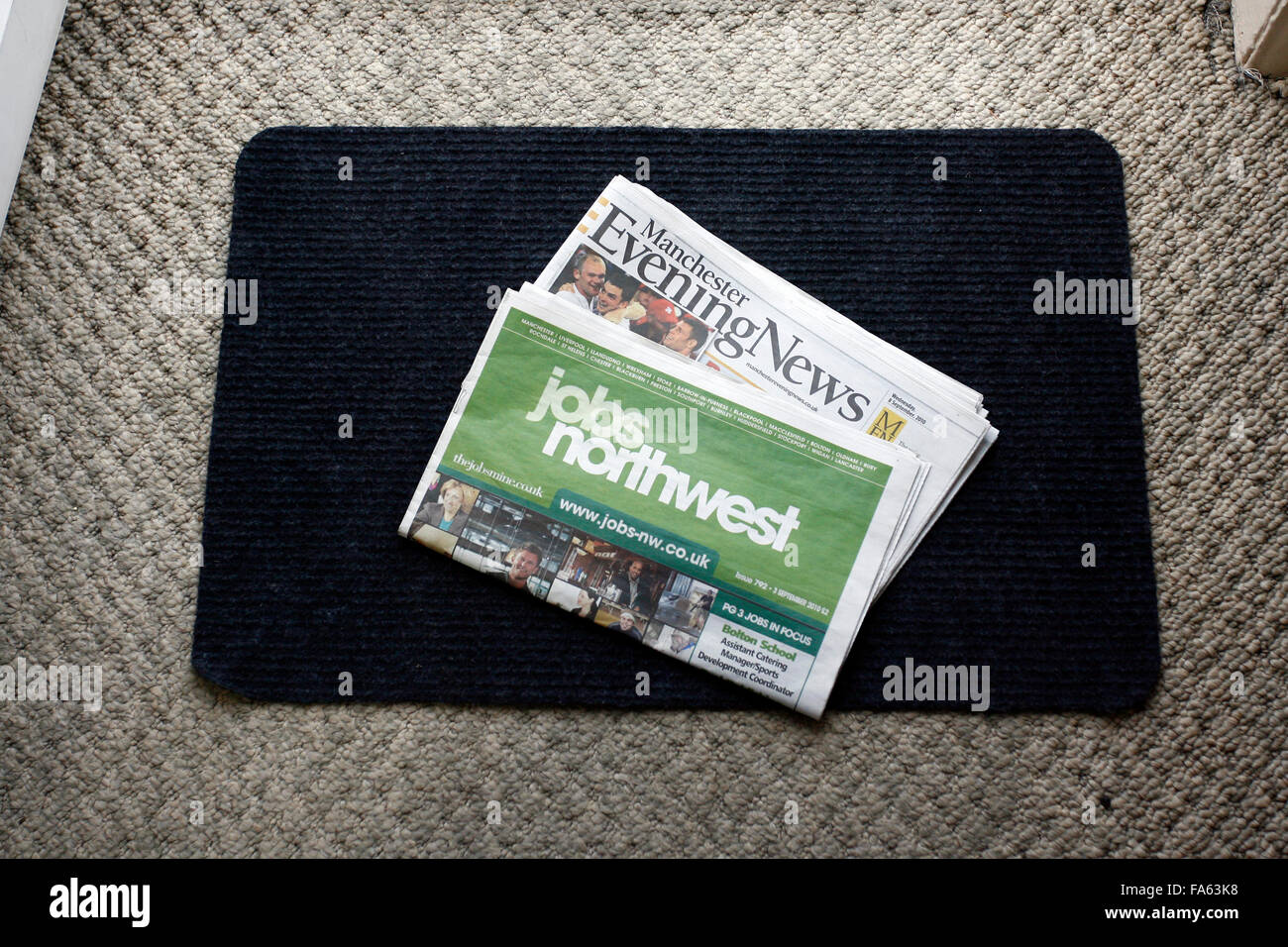 Manchester Evening News and Jobs Northwest supplement  newspaper on a doormat - Stock Image