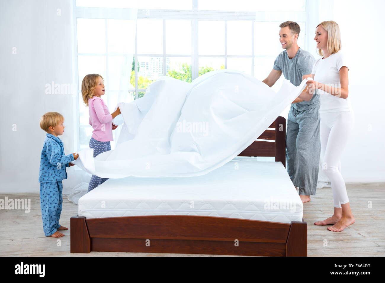 Young nice family making bed - Stock Image