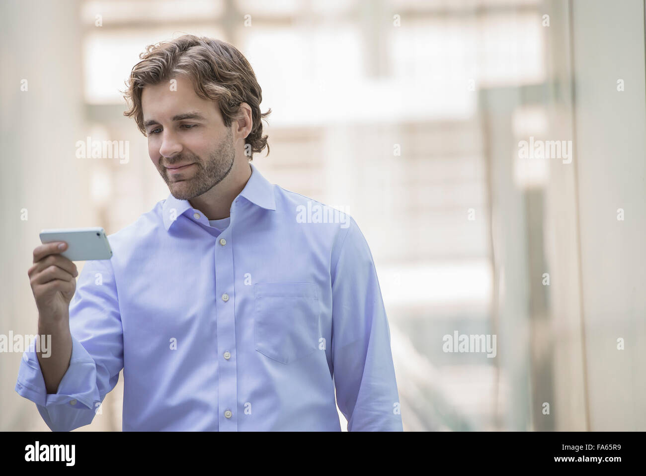 A man in shirt and tie using a smart phone in an urban scene. Stock Photo