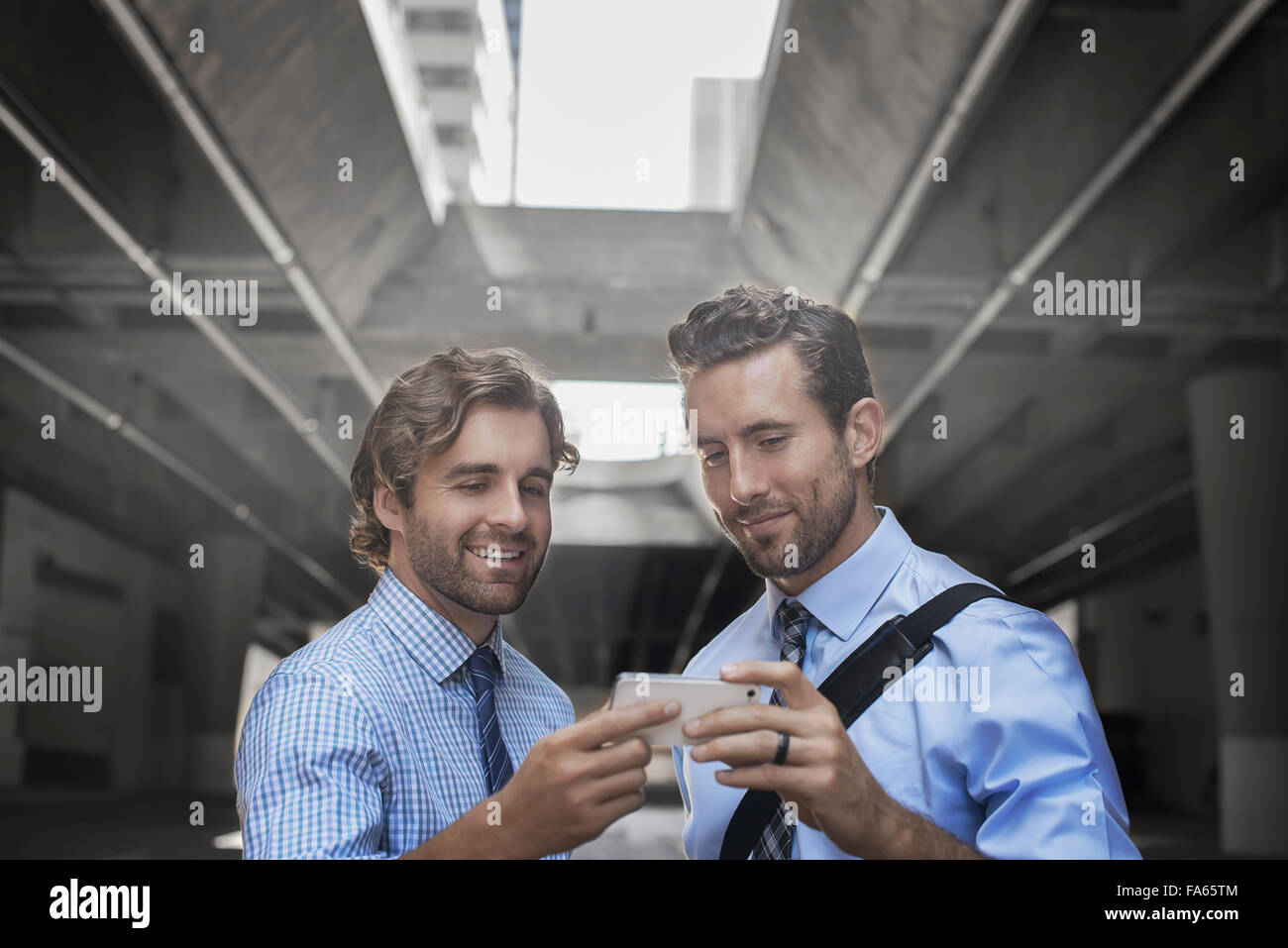 Two men in shirts and ties taking a selfie with a smart phone, with an urban walkway and tall buildings in the background. - Stock Image