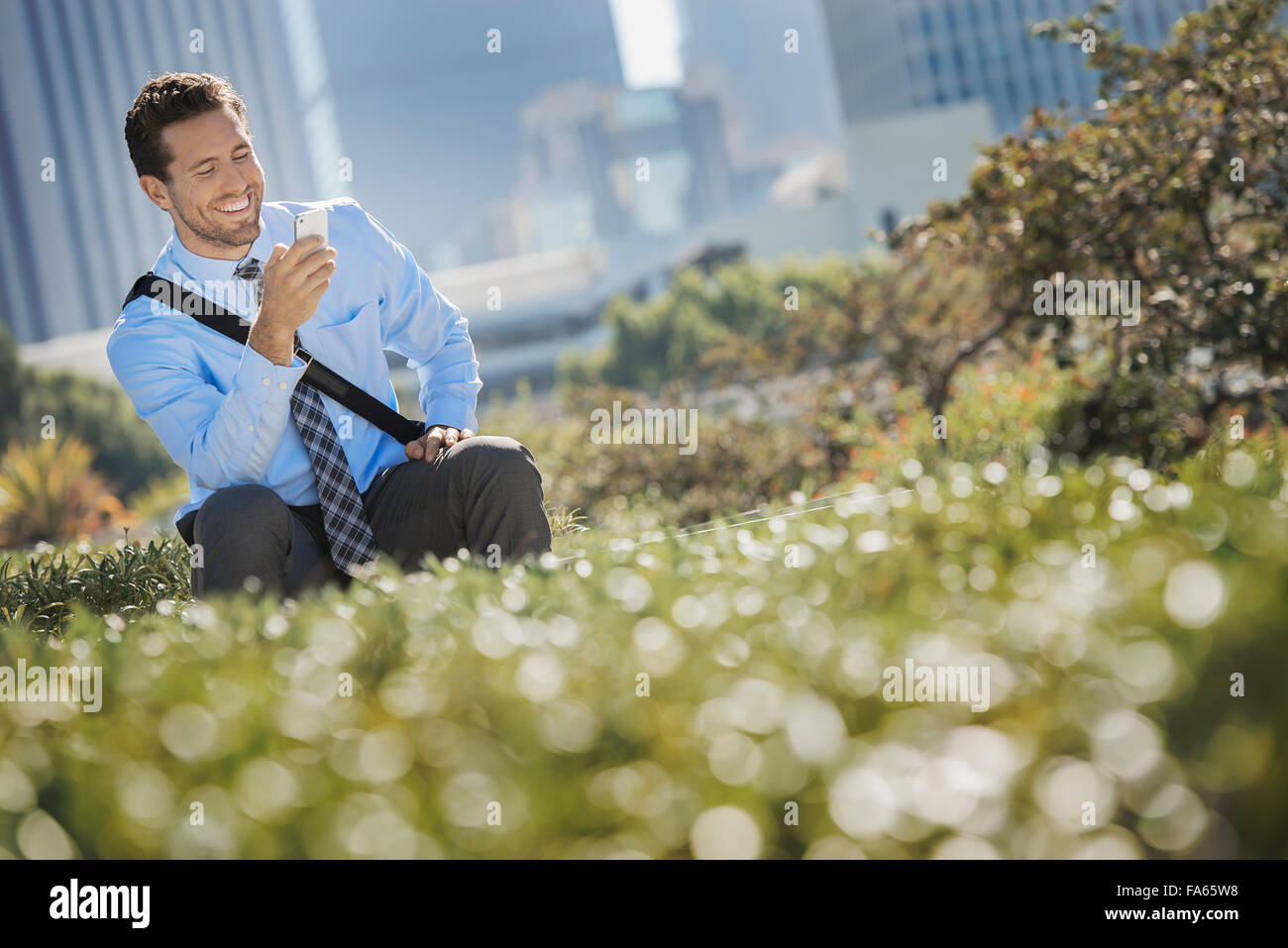 A young man on a park bench in the city, using a cell phone. Stock Photo