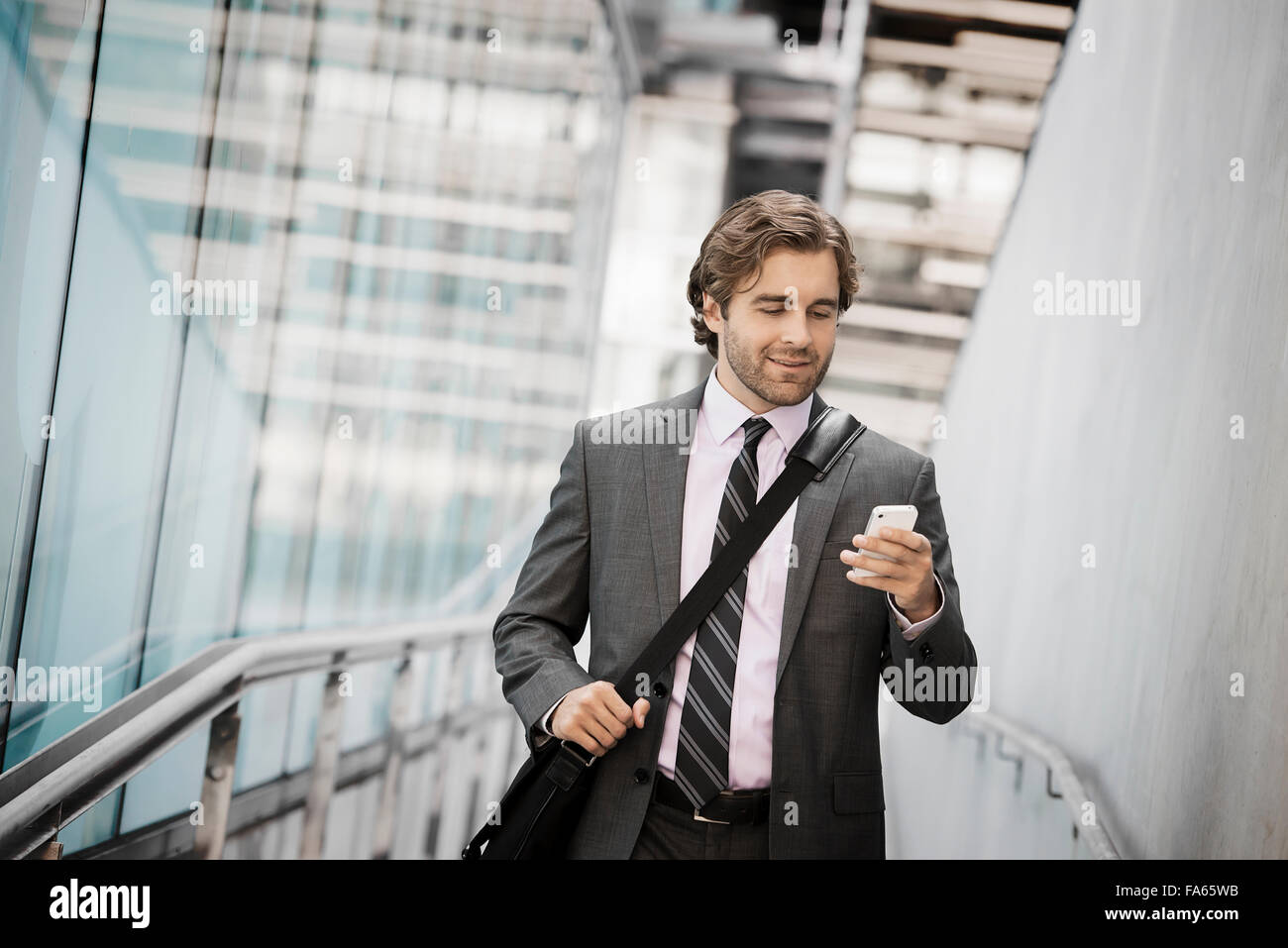 A man carrying a computer bag with a strap on a city walkway looking at his smart phone. - Stock Image