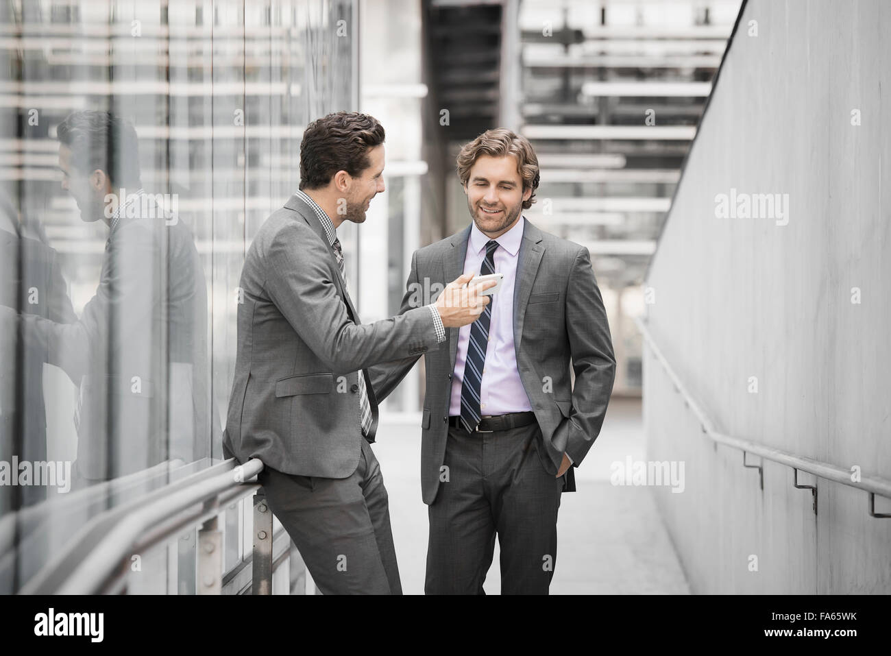 Two men in business suits outside a large building, one holding a smart phone. - Stock Image