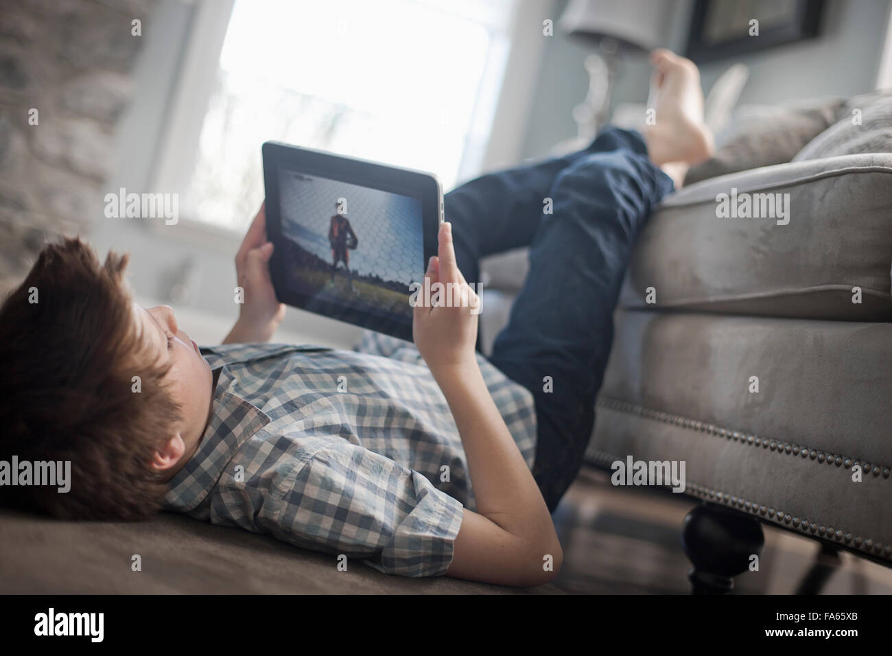 A boy lying on his front on the floor, looking at a digital tablet. - Stock Image