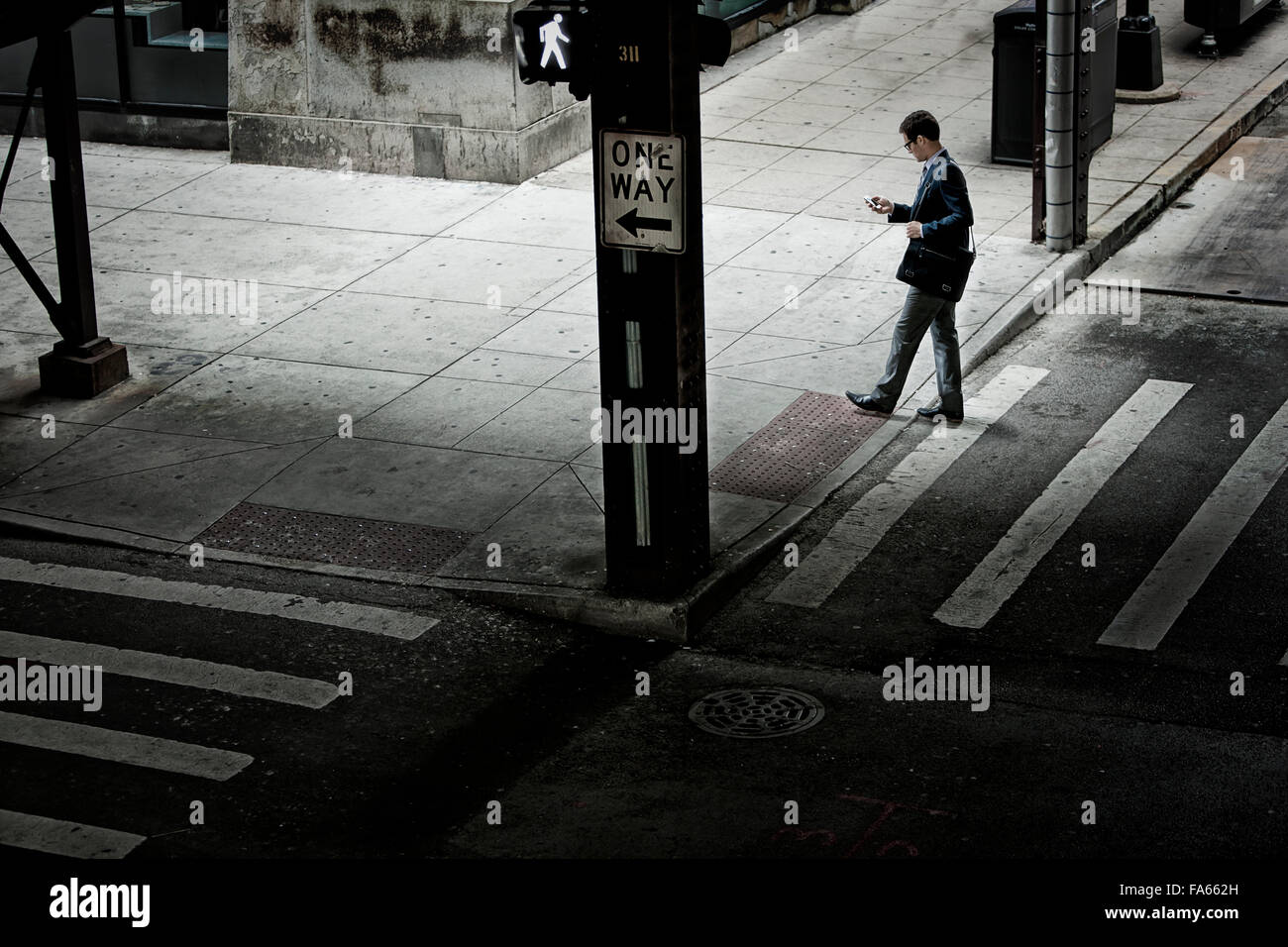 A man walking across a street crossing, looking at a phone in his hand. - Stock Image