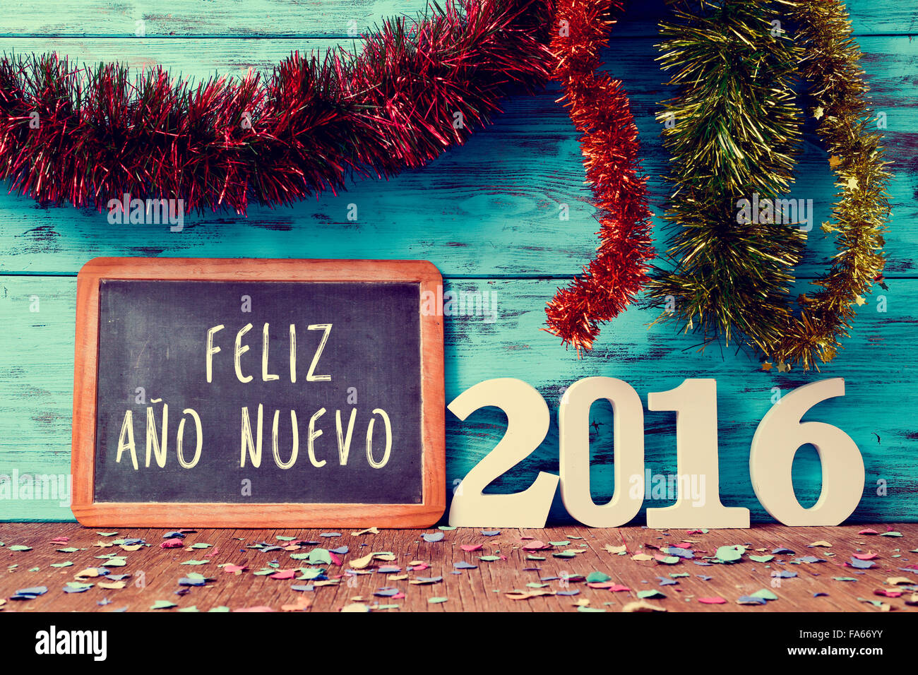 tinsel of different colors and a chalkboard with the text feliz ano nuevo, happy new year in spanish, and white - Stock Image