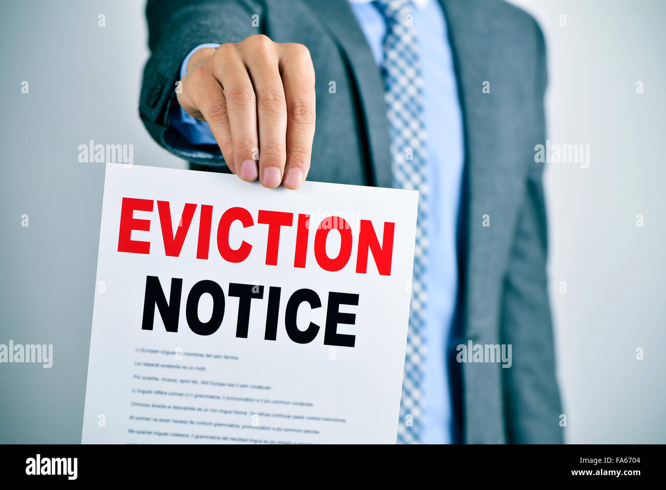 a young caucasian man wearing a gray suit shows a document with the text eviction notice - Stock Image