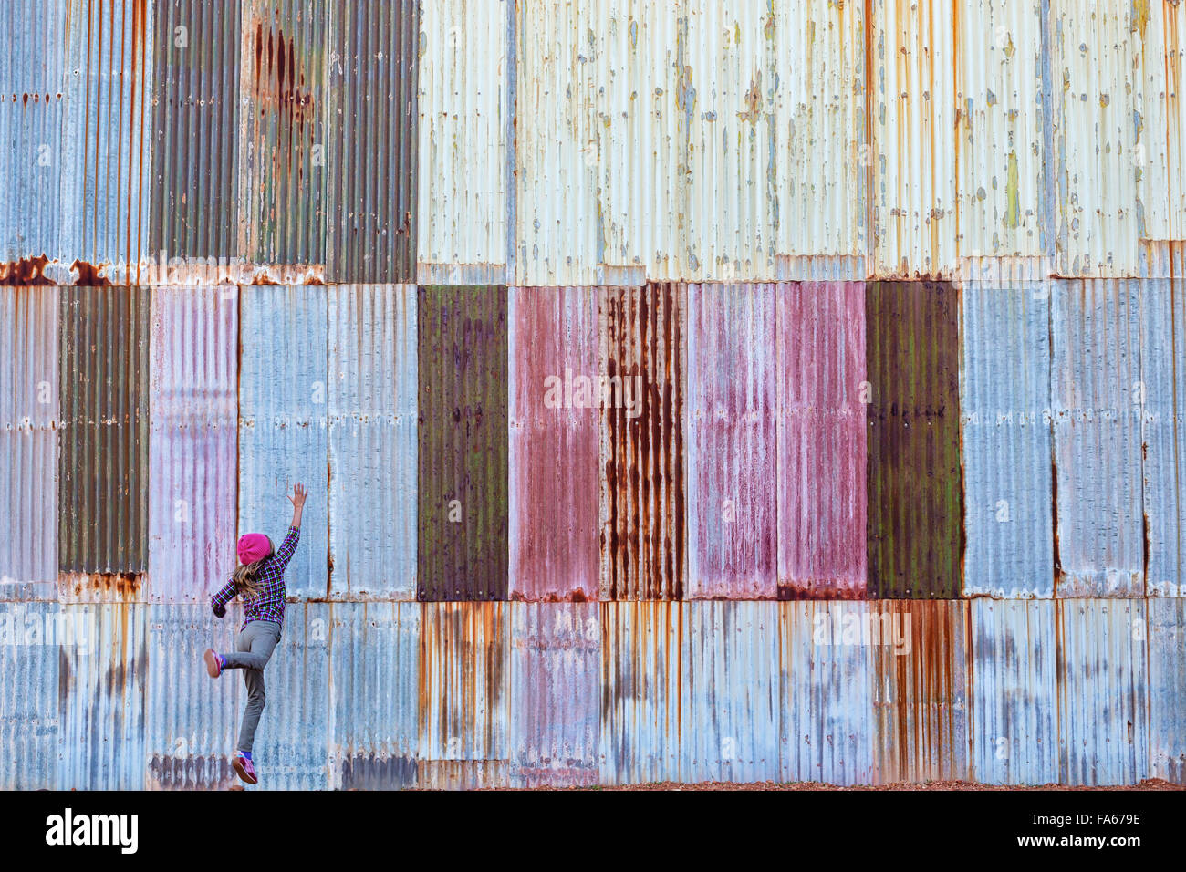 Girl jumping in front of a colorful corrugated metal wall, Kalgoorlie, Western Australia - Stock Image