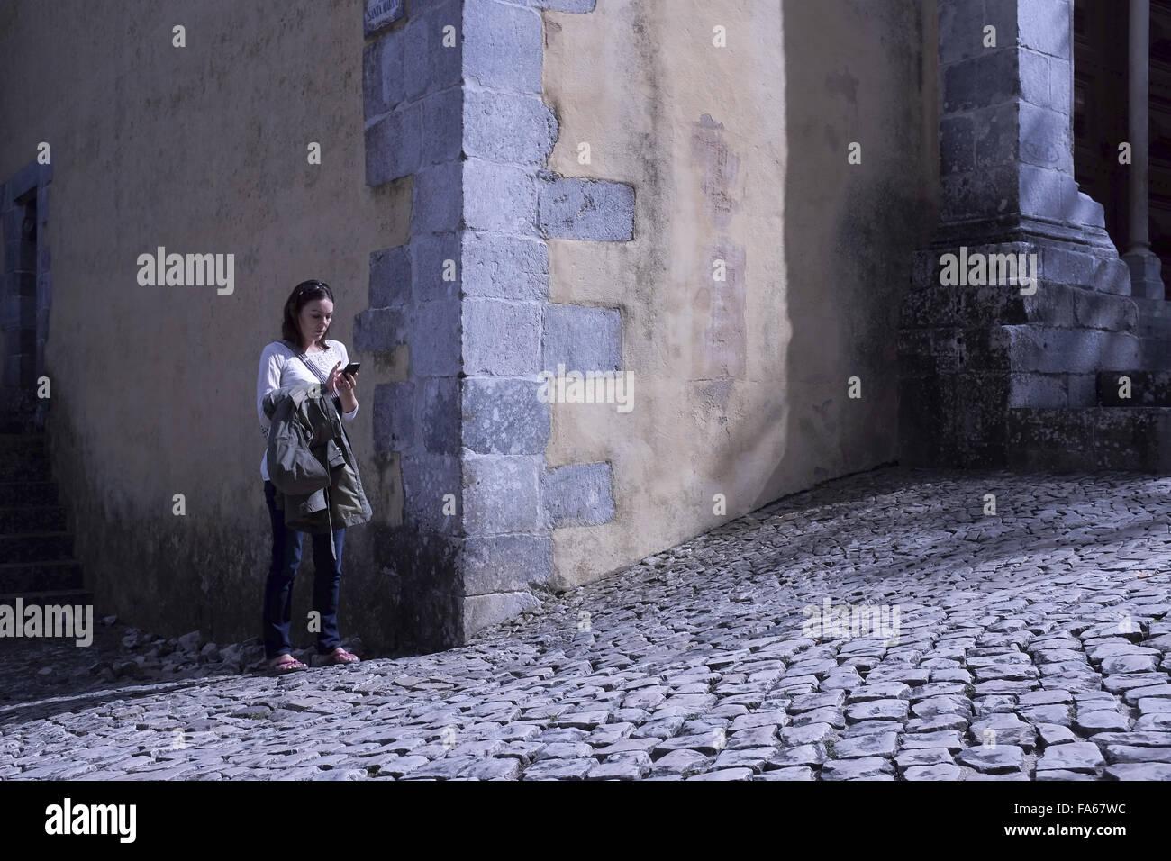 Woman standing in street text messaging, Lisbon, Portugal - Stock Image