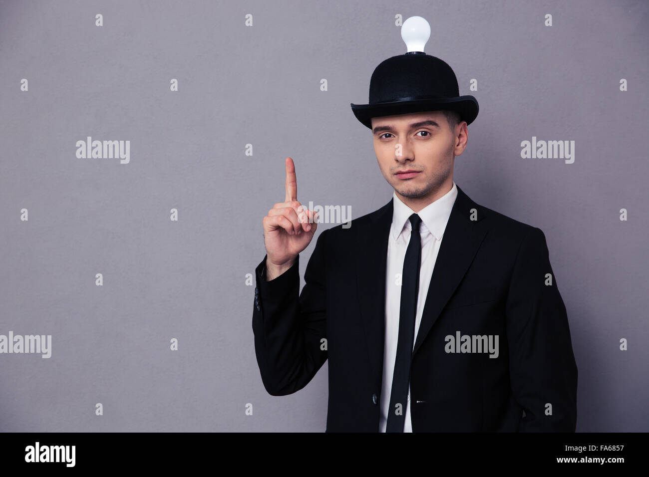 Portrait of a young businessman having idea over gray background - Stock Image