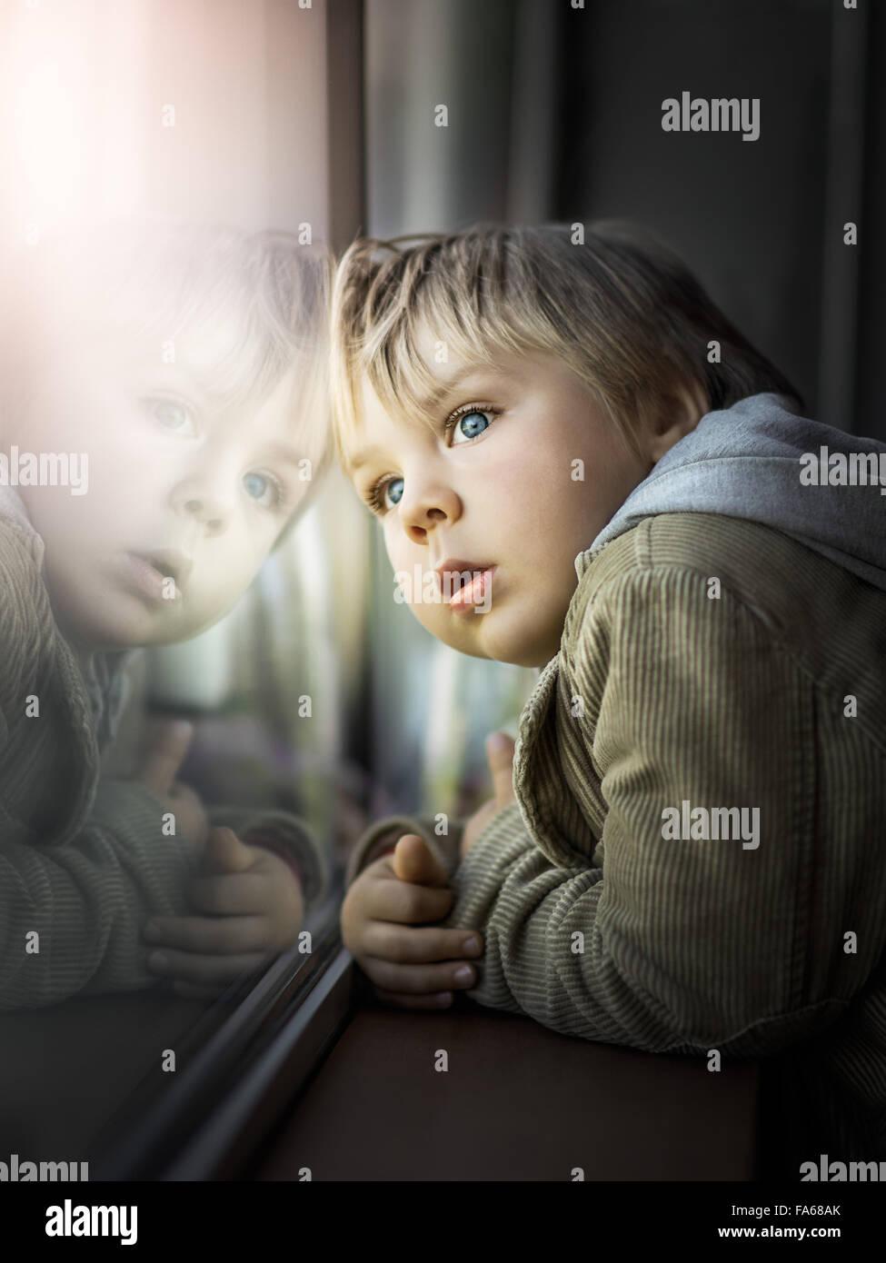 Boy looking through window - Stock Image
