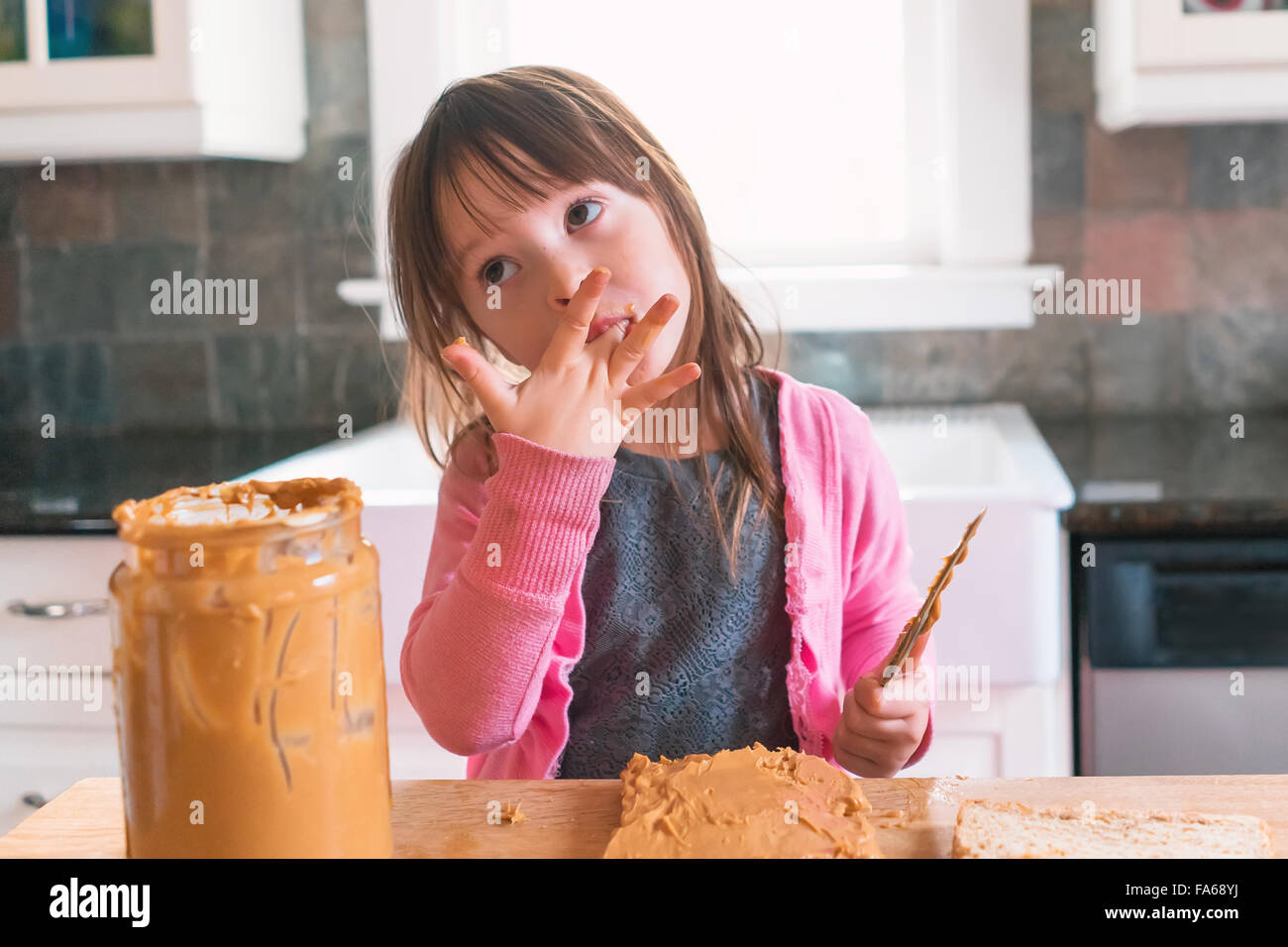 Girl making peanut butter sandwich, licking fingers - Stock Image