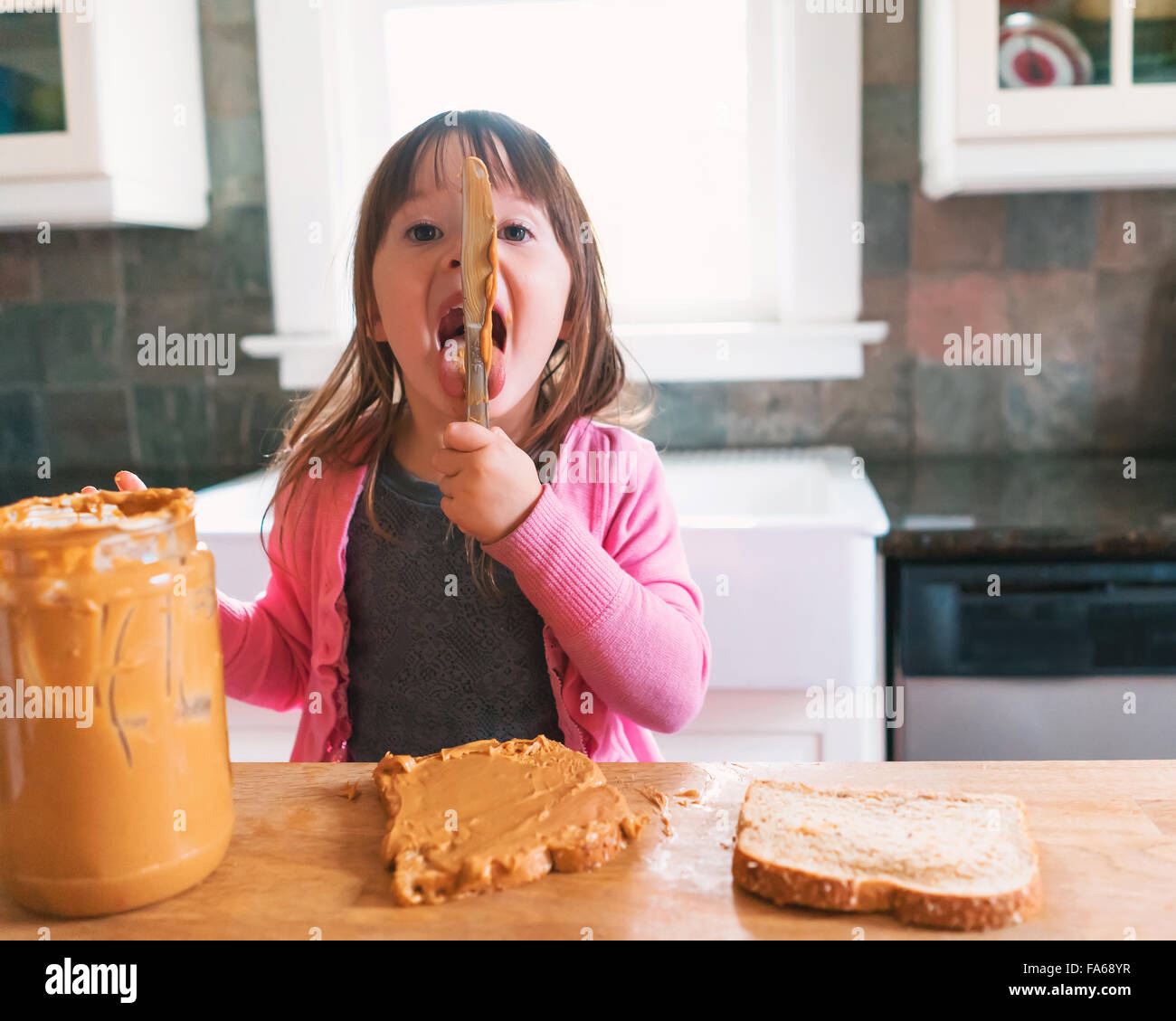 Girl making a peanut butter sandwich, licking the knife - Stock Image