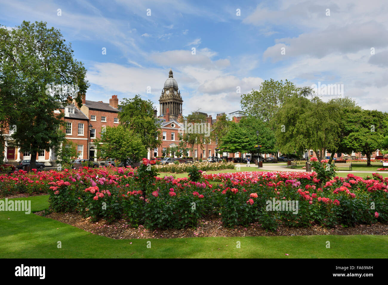 Park Square Leeds, with the clock tower of Leeds Town Hall visible in the background, Leeds, West Yorkshire, England - Stock Image