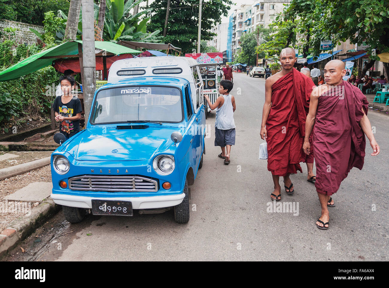 buddhist monks and taxi on street in yangon myanmar - Stock Image