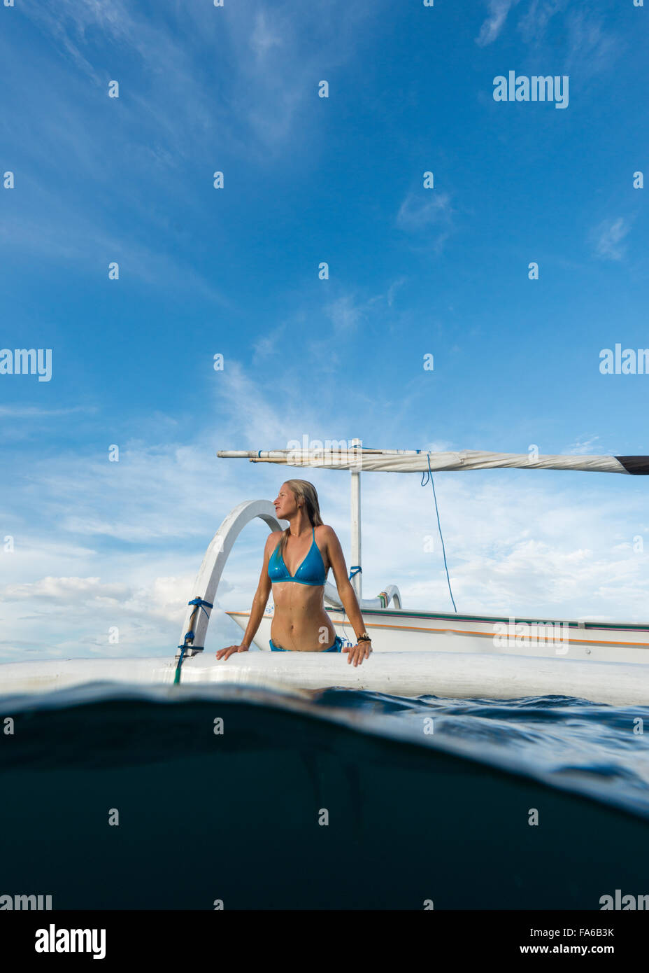 Woman getting out of the sea onto a boat, Bali, Indonesia - Stock Image