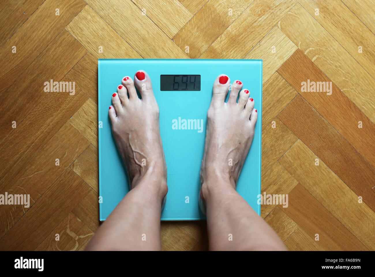 Woman standing on weighing scales - Stock Image