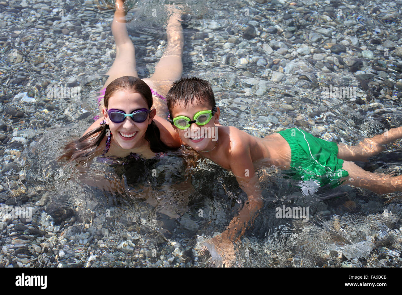 Boy and girl lying in shallow water at beach - Stock Image
