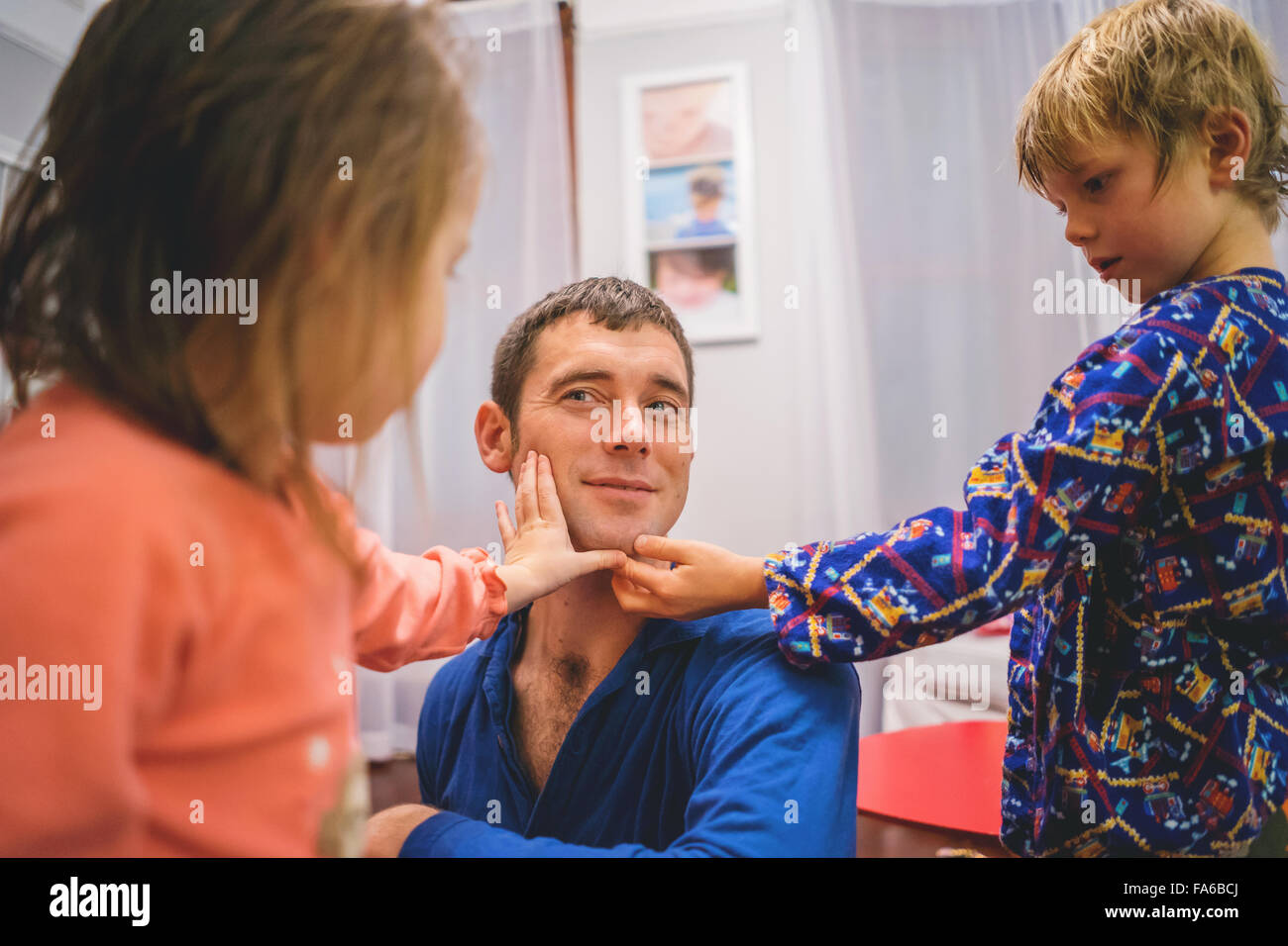 Boy and girl touching man's shaved face - Stock Image