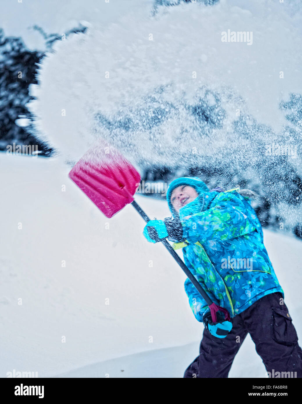 Girl shoveling snow in the yard with a spade - Stock Image