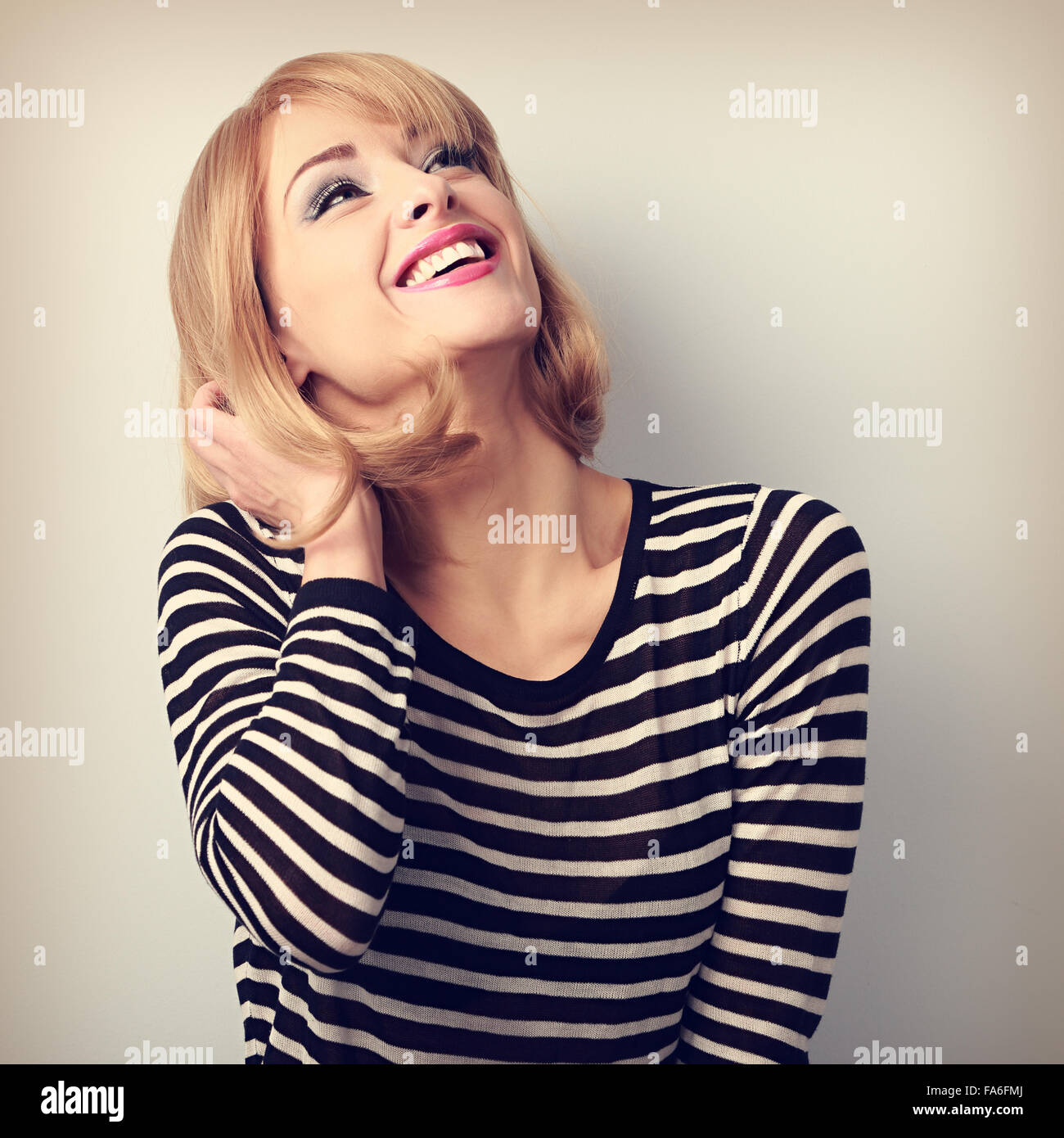 Happy laughing young blond woman looking up. Vintage closeup portrait - Stock Image