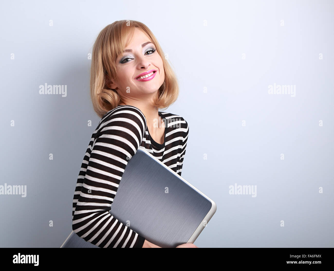 Happy smiling casual woman holding in hand laptop on blue background with empty copy space - Stock Image