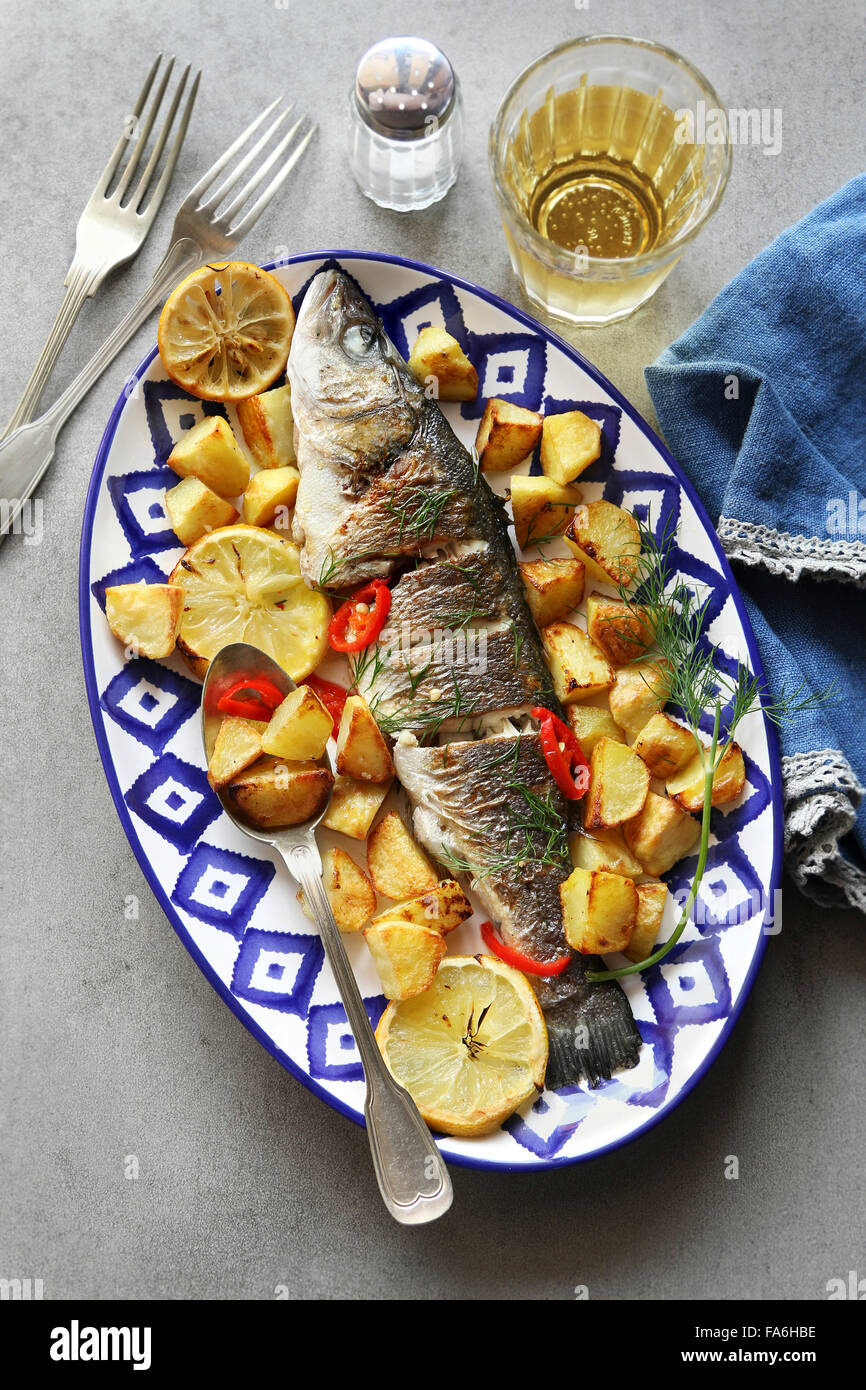 Oven-baked Sea bass fish with lemon and potatoes - Stock Image