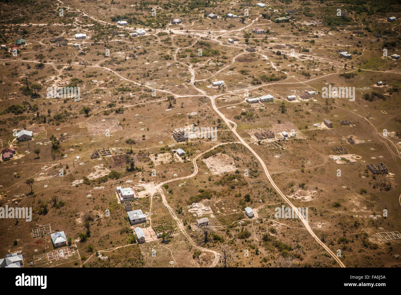 Many roads across Tanzania still lack pavement, such as these outside Tanga. - Stock Image