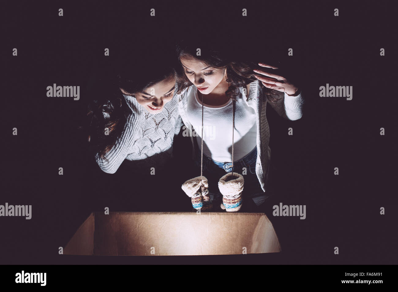 Sisters opens box with a Christmas present - Stock Image