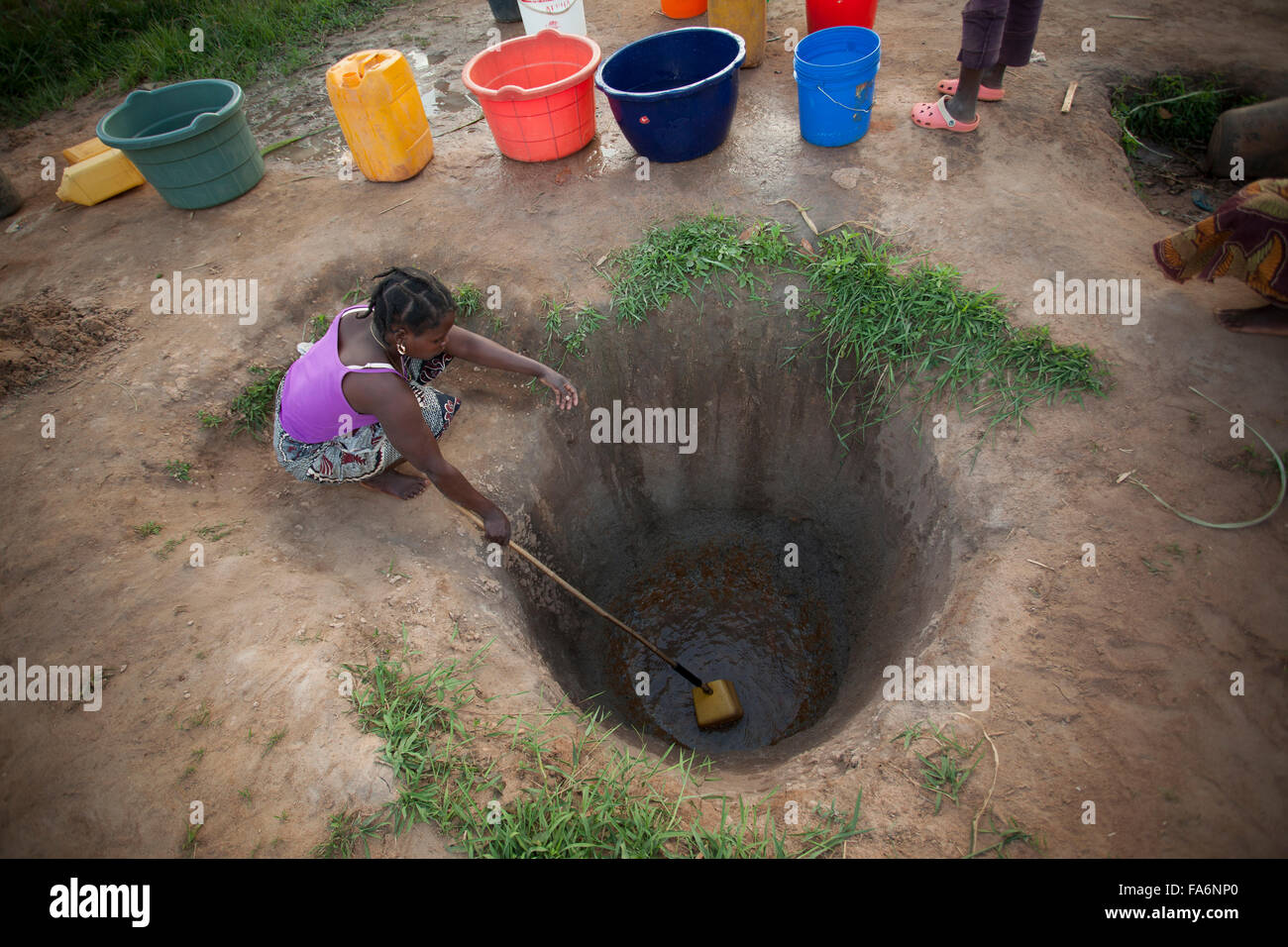 Residents draw muddy water from hand-dug wells in Nampula, Mozambique. - Stock Image