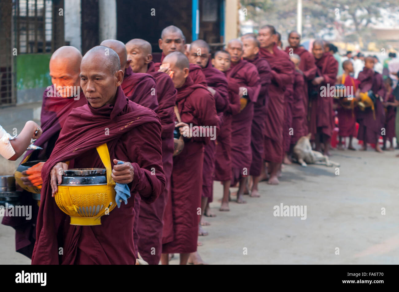 Buddhist monk in a long queue in Shwe Kyet Yet village in Mandalay Region, Myanmar, is given food into his alms - Stock Image