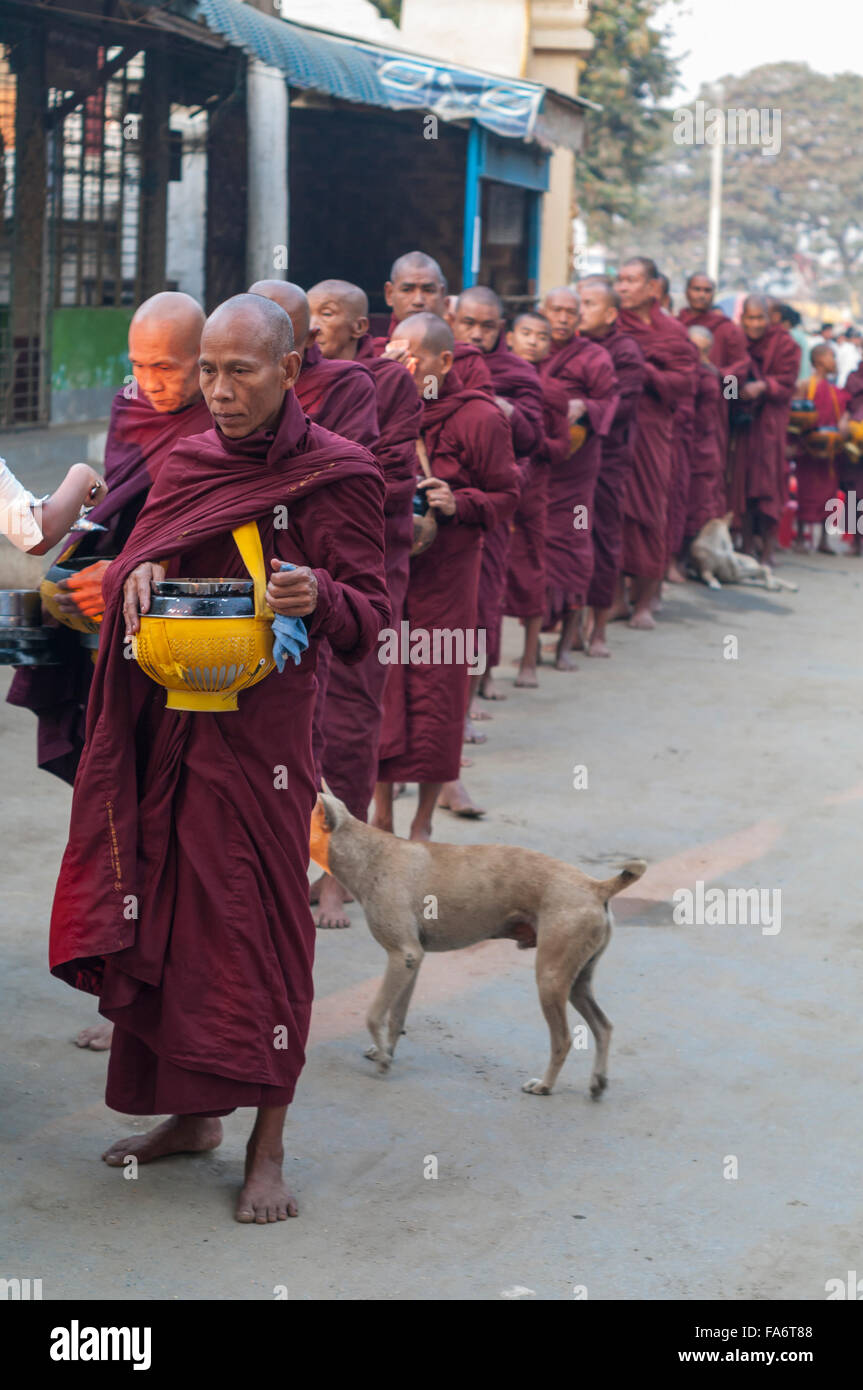 Buddhist monk in a long queue in Shwe Kyet Yet village in Mandalay Region, Myanmar, receiving food into his alms - Stock Image
