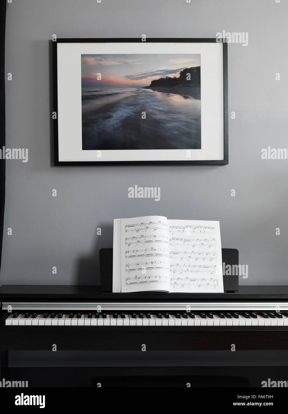 Digital piano keyboard with music scores in a room interior - Stock Image