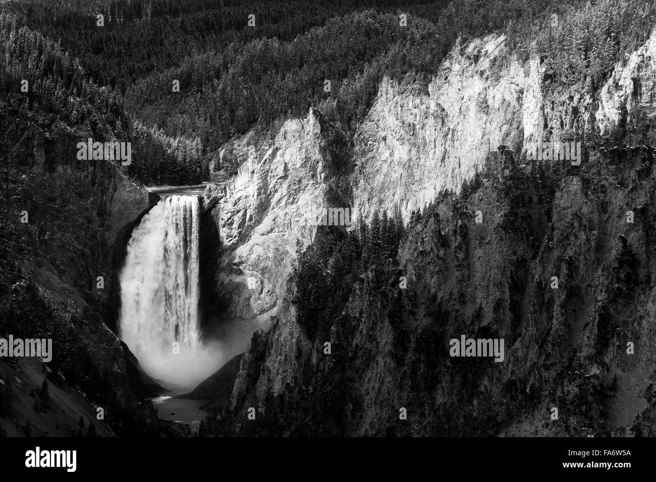 Sunlight breaks through clouds to light up Lower Falls of the Yellowstone River and a small side canyon of the Grand - Stock Image