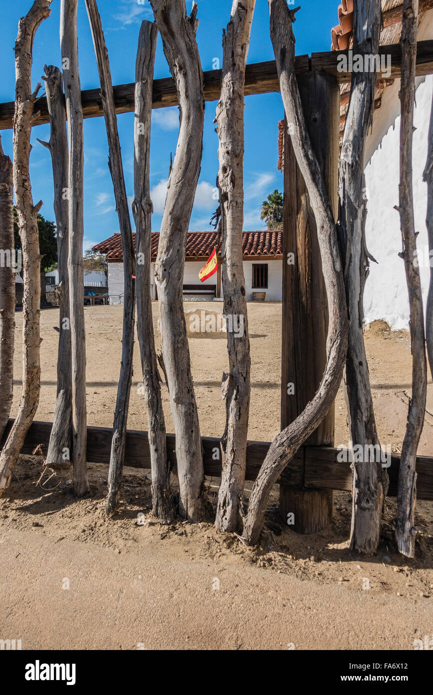 A primitive style fence made out of tree branches in the foreground at the Santa Barbara Presidio, a reconstruction - Stock Image